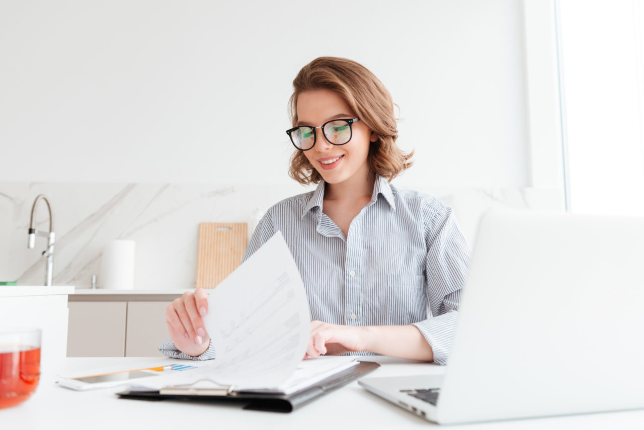 Photo of cheerful attractive woman in glasses reading new contra